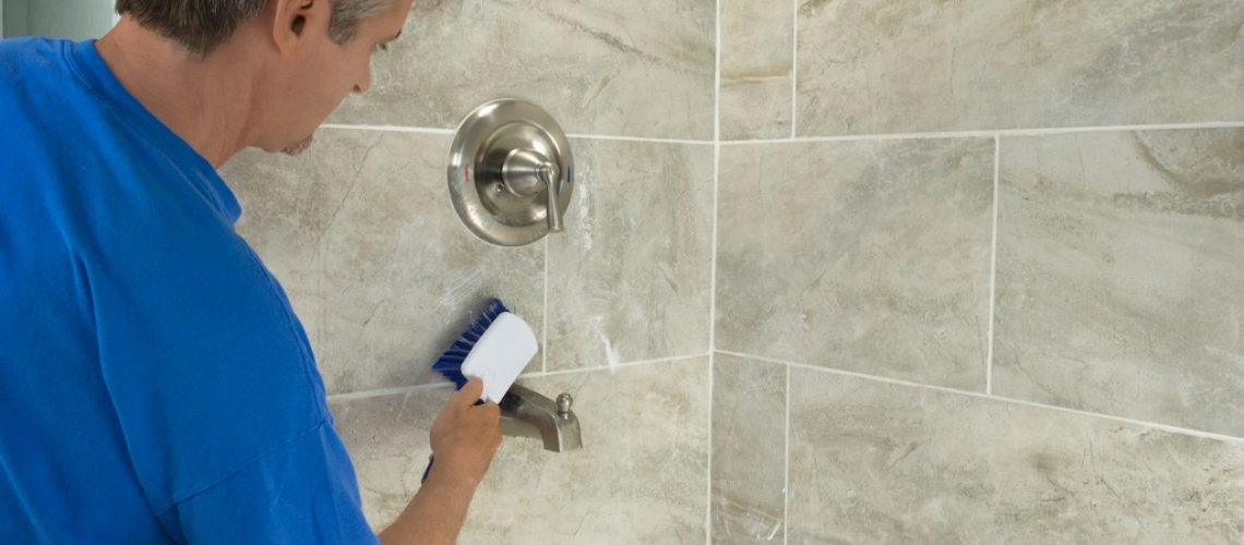 A man doing household chores is cleaning bathroom bathtub tiles and fixtures with a soapy white scrub brush.