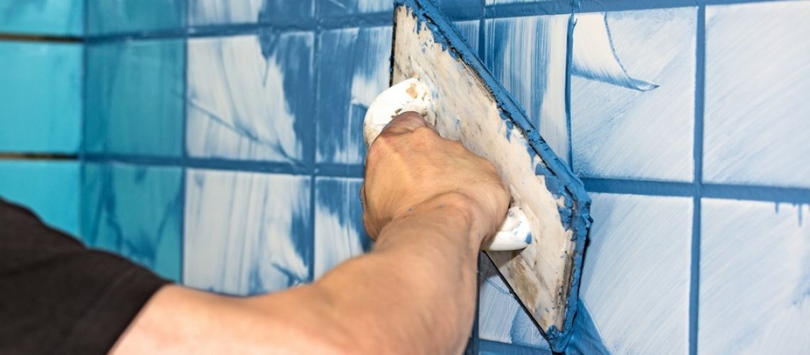 Workman or builder applying blue grout to white interior tiles in a house in a concept of DIY or decorating, close up view of his arm.