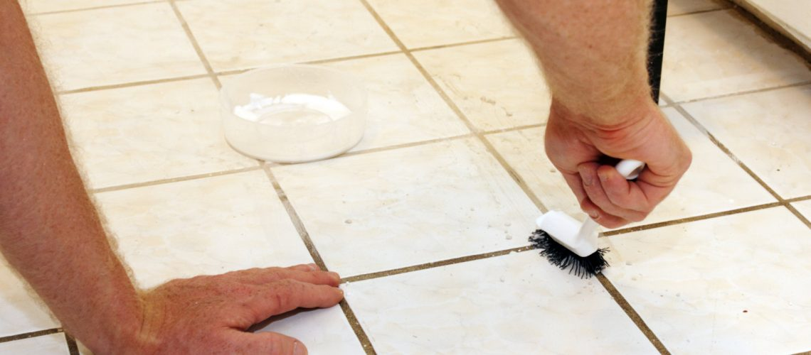 Two caucasian male hands cleaning kitchen grout of an old, dirty tile floor with environmentally friendly hydrogen peroxide, baking soda and a scrub brush.